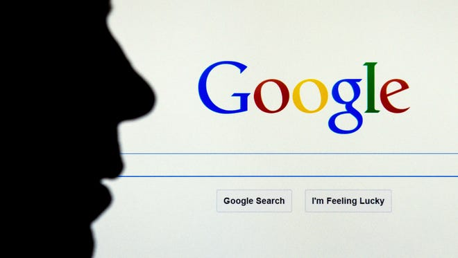 A person sits in front of home page for Google search.