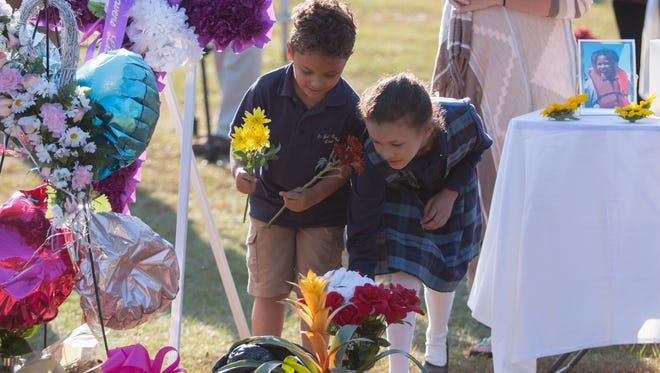 Jameson Swindelle, 6, and his sister, Jenecia, 9, place flowers on the grave of 9-year-old Dericka Lindsay, a student at St. John the Evangelist School, during a memorial service Thursday, Nov. 16, 2017, at Resthaven Gardens Cemetery in Pensacola.