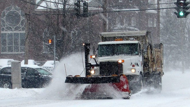 A plow clears snow from Madison Avenue in Elmira last winter. Public works services are among functions currently shared between the City of Elmira and Chemung County.