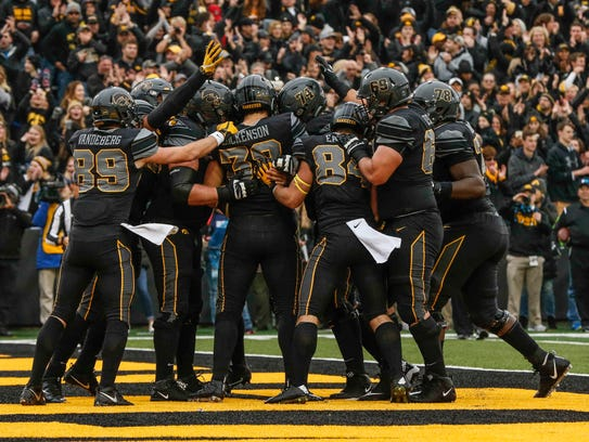 Members of the Iowa football team celebrate after tight