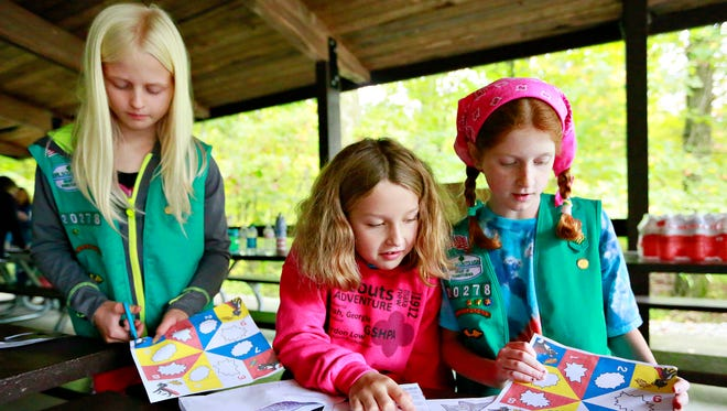 From left, Elliot Carter, 10, Lily Rower, 9, and Clare Seifert, 9, all of Troop 20278 in Manchester Township, make fortune-tellers as multiple scout troops gather during a fall product kickoff event at Rocky Ridge Park in Springettsbury Township, Saturday, Oct. 14, 2017. Dawn J. Sagert photo