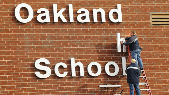 Norm Williams steadies a ladder as Jim Kouns hangs letters for Oakland High School Friday, December 3, 2010, at the former Oakland Elementary School. Oakland High School opens for classes in the fall of 2011. Both men are with Williams Signs Inc., Lafayette.