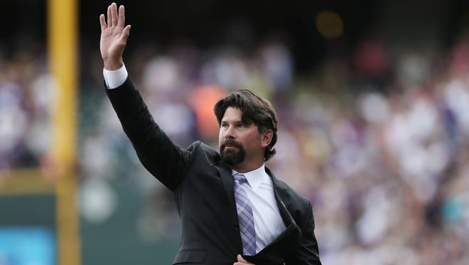 Retired Colorado Rockies first baseman Todd Helton waves at the crowd after his jersey number was retired during a ceremony on Sunday.