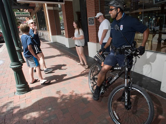 Pensacola Police Department Office Greg Gordon talks with the Dees family on Friday, June 2, 2017, while he is out on bicycle patrol in the downtown area.
