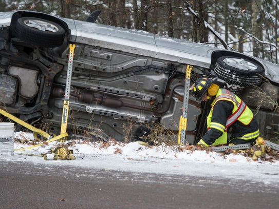 Burlington firefighters work to secure a car that rolled