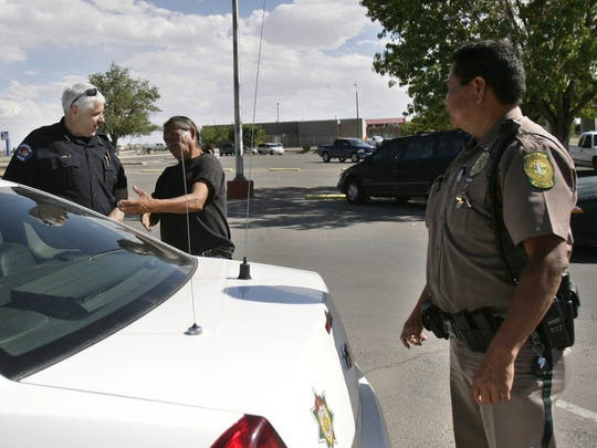 Farmington police Chief Steve Hebbe, left, and Shiprock police Lt. Phillip Joe speak with a man Aug. 7, 2014, at the City Market parking lot in Shiprock.