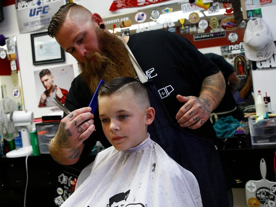 Jesse Rogers cuts Bryce Sandoval's hair on Wednesday at Main Barber Shop II in Farmington.