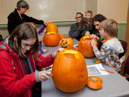 A group of parents and kids use their carving skills to contribute their works  to the Humboldt Park Pumpkin Pavilion.