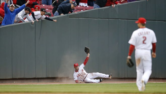 Cincinnati Reds center fielder Tyler Holt (40) shows the ball after making a diving catch down the left-field line in the top of the ninth inning of the MLB Opening Day game between the Cincinnati Reds and the Philadelphia Phillies at Great American Ball Park on Monday, April 4, 2016. The Reds rallied to beat the Phillies 6-2 on Opening Day.