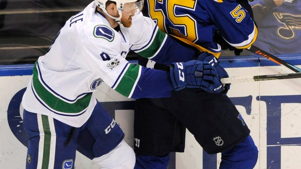 St. Louis Blues' Colton Parayko (55) is checked by Vancouver Canucks' Jack Skille (9) during the second period of an NHL hockey game, Thursday, Feb. 16, 2017, in St. Louis. (AP Photo/Bill Boyce)