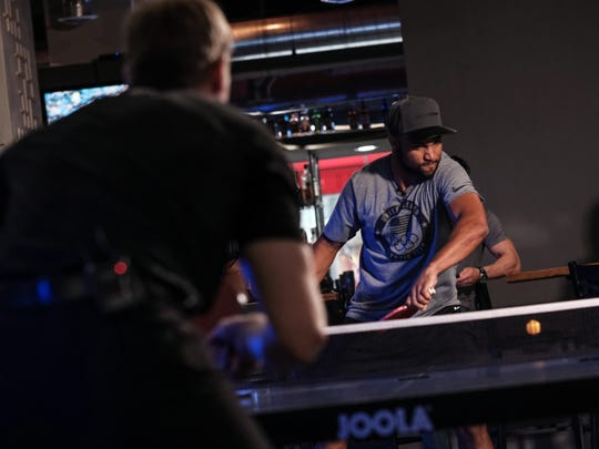 Detroit Lions wide receiver Golden Tate returns the ball back to IndyCar driver Josef Newgarden during a ping-pong battle at Drive on Monday, May 30, 2018 in downtown Detroit.