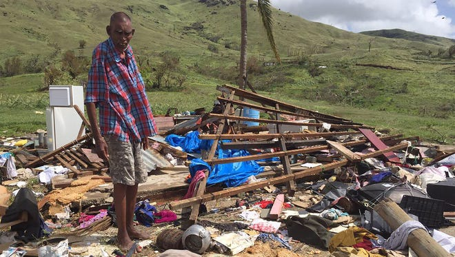 This handout photograph taken on February 22, 2016 and provided by 'Mai Life' magazine shows resident Naresh Kumar standing over the ruins of his house following Cyclone Winston in western Fiji's Tuvu Lautoka.