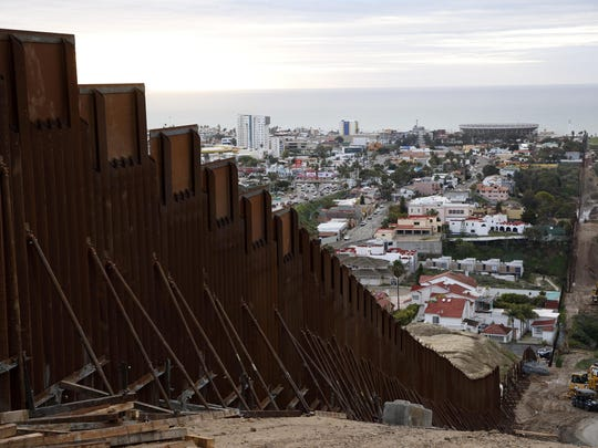 In this Jan 15, 2019 image, a section of newly-replaced border wall separates Tijuana, Mexico, above left, from San Diego, right, in San Diego. Border Patrol officials say some Mexican homes and structures encroach on U.S. soil posing a dilemma for authorities when replacing the wall.