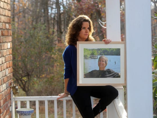 Nancy Montgomery holds a photo of her husband, Jim Lovell, an NBC sound technician who was killed aboard the Metro-North train that derailed at Spuyten Duyvil on Dec. 1, 2013.