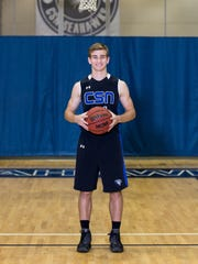 Community School of Naples basketball player Jake Kastroll poses for a photo on his team's home court.