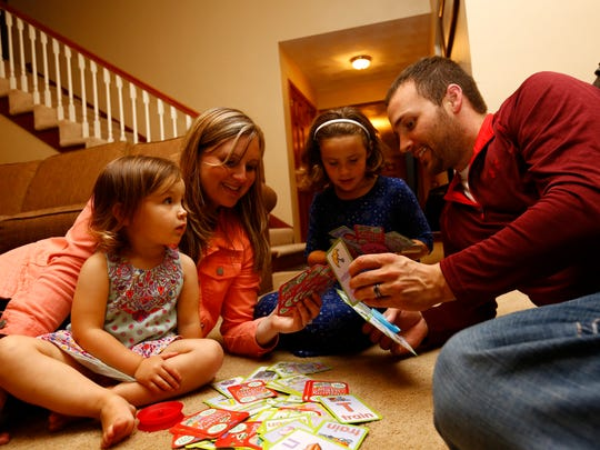 Jared Seubert, right, his 6-year-old daughter Tyla, wife Bethany, and 2-year-old daughter Kali, play a card game. Wednesday, Sept. 21, 2016, at their parents' home in Marathon.