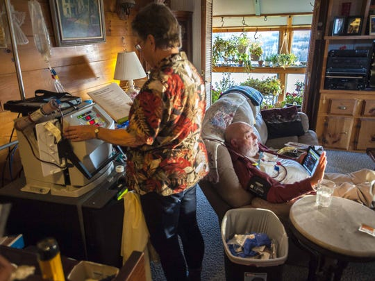 Con Hogan, right, a member of the Green Mountain Care Board, needs a kidney transplant.  His wife Jeannette tends to the dialysis machine he is hooked up to at home in Plainfield on Wednesday, November 18, 2015.