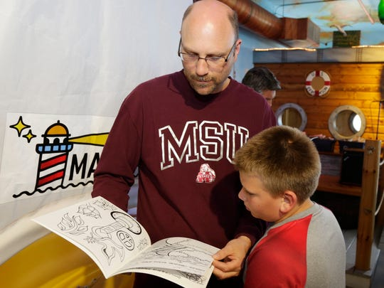 """Dale Bogenschuetz, left, looks over """"Color Me Sheboygan"""" with his son Asher, 11, at the premier of the coloring book by Katie English Wednesday May 31, 2017 at the Above and Beyond Children's Museum in Sheboygan, Wis."""