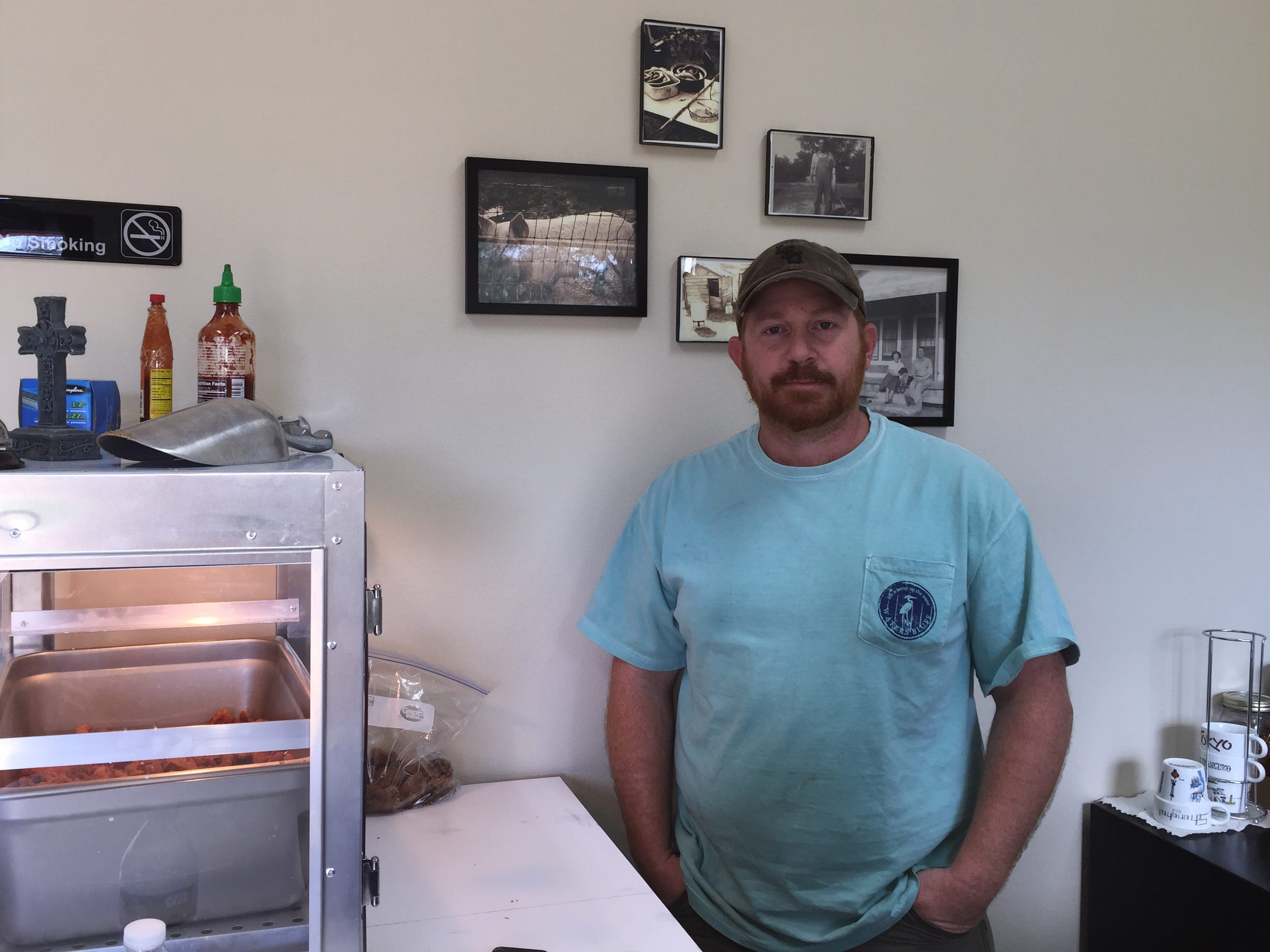 Adam Walker stands in front of vintage family photos of a boucherie at T-Red's Cajun Cuisine in Dubach.
