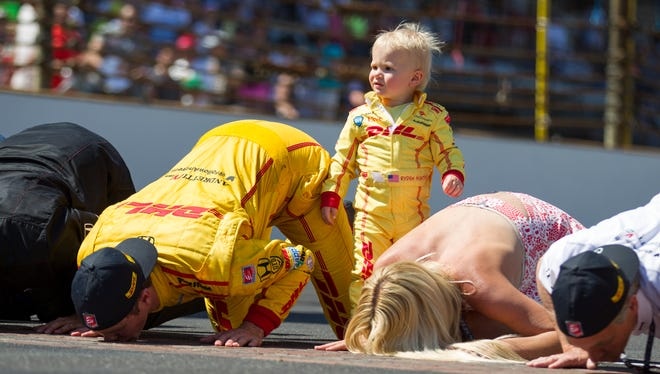 Ryden Hunter-Reay, the son of driver Ryan and wife Beccy, stands as the couple kisses the bricks following Hunter-Reay's victory at the Indianapolis Motor Speedway, Sunday, May 25, 2014.