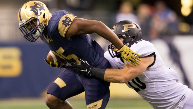 Tarean Folston, running back for Notre Dame, is brought down by Sean Robinson, linebacker for Purdue against Notre Dame football at Lucas Oil Stadium, Indianapolis, Saturday, September 14, 2014.