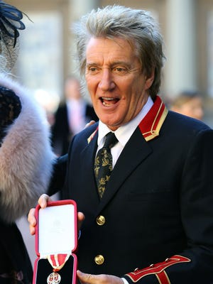 Rod Stewart, seen here with his knighthood medal from Queen Elizabeth II in December, is being criticized for a video of a mock execution in the desert of Abu Dhabi.
