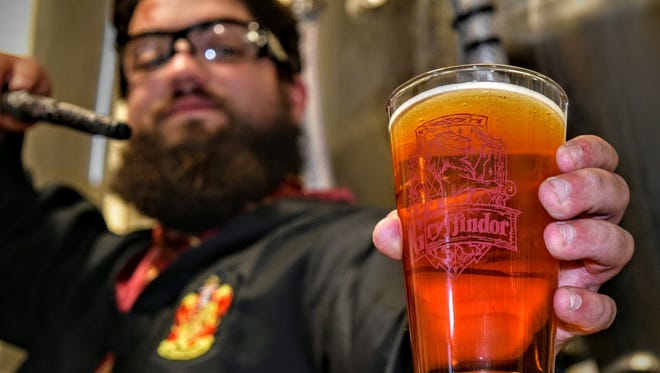 """Mispillion River Brewing's Brandon Gouge with a glass of """"Harry Potter""""-themed beer."""