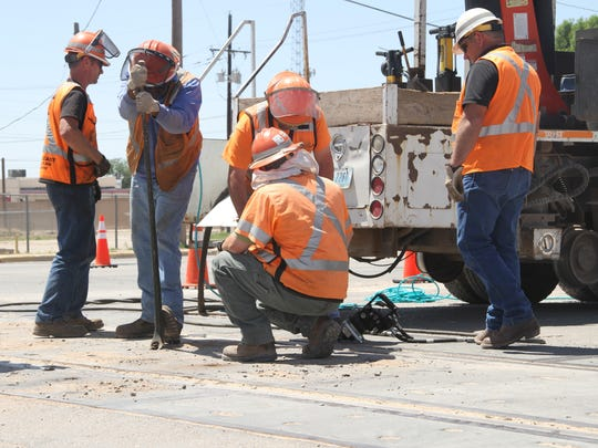 Laborers work on a railroad crossing on Green Street following a BNSF train colliding with a semi truck Monday morning. The construction, which has consolidated roads to one lane going east and west, is not related to the collision.