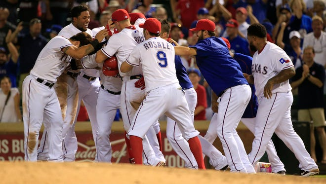 Texas Rangers designated hitter Josh Hamilton (32) is mobbed by teammates after hitting the game winning single against the New York Yankees during the ninth inning at Globe Life Park in Arlington.