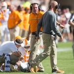 Tennessee head coach Butch Jones talks with Tennessee defensive backs coach Willie Martinez while  defensive back Malik Foreman (13) is tended too during the first half of the game against Texas A&M on Saturday, October 8, 2016. (SAUL YOUNG/NEWS SENTINEL)