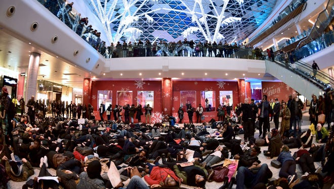 """A group of protesters stage a """"die-in"""" at the Westfield shopping center in support of U.S. demonstrations over the killing of unarmed black men by white officers, in West London on Dec. 10."""