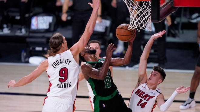 Boston Celtics guard Kemba Walker (8) takes a shot between Miami Heat's Kelly Olynyk (9) and Tyler Herro (14) during the second half of an NBA conference final playoff basketball game, Thursday, Sept. 17, 2020, in Lake Buena Vista, Fla.