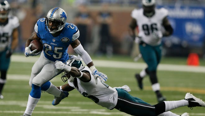 Detroit Lions' Theo Riddick runs out of the tackle of Philadelphia Eagles' Walter Thurmond III on a first down run in the first quarter on Thursday, November 26, 2015, in Detroit.