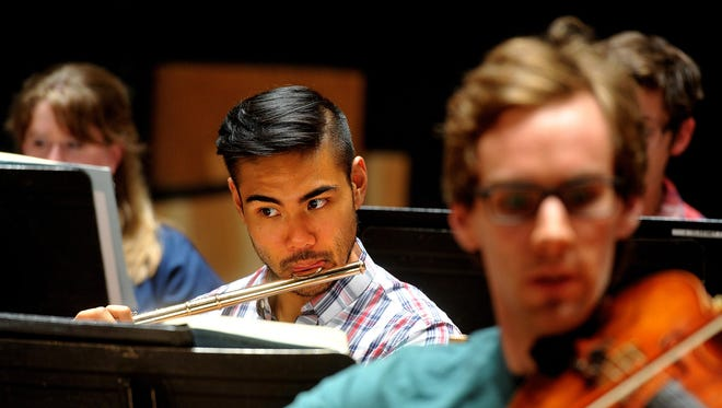 """Flutist Norman Gonzalez rehearses Tchaikovsky's """"Sleeping Beauty"""" with the Great Falls Symphony at the Mansfield Theater in September."""