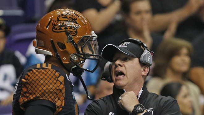 Rattlers' head coach Kevin Guy talks to quarterback Nick Davila during the game against the Thunder at the US Airways Center in Phoenix, AZ on April 18, 2015.