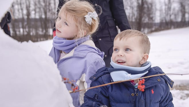 From the archive: Julia and Cole Koomem, of Pittsford, make a snowman on the hill overlooking the Hundred Acre Pond during the Mendon Ponds Winterfest (Jan. 19, 2015).