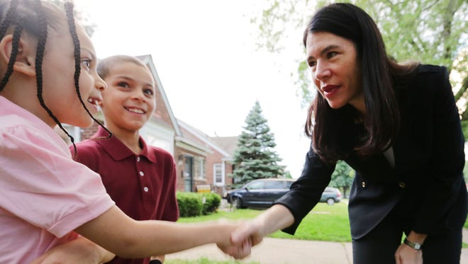 Chiara Steward, left, 8, and her  brother Derrick Steward, 10, meet  Detroit Public Schools' Interim Superintendent Alycia Meriweather, who is at their home in Detroit  to meet them and walk with them to their  school, Casimir Pulaski Elementary, on their first day, Tuesday, Sept. 6, 2016 in Detroit.