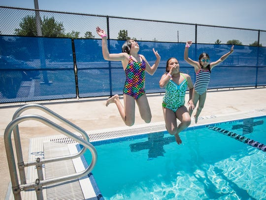Free swim days are set for July 4 and Labor Day. 11-year-old Celine Muñoz, left, 10-year-old Victoria Ballesteros and 8-year-old Jaylynn Sapien leap into the water at Laabs Pool in 2016.