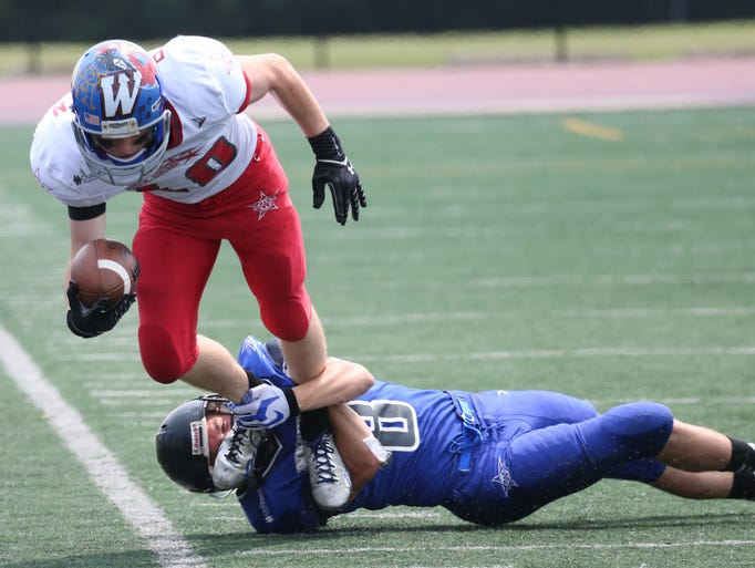 North's Nathan Slenczka (8) takes down ball carrier South's Cullen Pedersen (10) during Saturday's Division 4-7 All Star football game at J.J. Keller Field of Titan Stadium.
