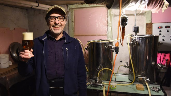 Manny Holl, pictured in front of his homebrewing system and a glass of his own maibock beer in the basement of his City of Poughkeepsie home. Holl has been homebrewing for 27 years.