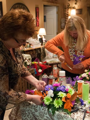 Michelle Jividen and Rebecca Wilburn, both of Oak Harbor, work on arrange fresh floral centerpieces for their Easter dinner table during a class at Audra's Florals in Oak Harbor on Wednesday evening.