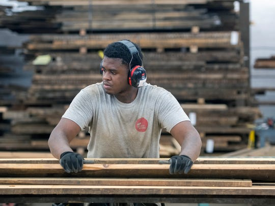 Working for Brick+Board, Kobe Bland stacks milled lumber in the company's Baltimore warehouse.