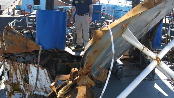 An NTSB investigator examines the wreckage of the tugboat Specialist Thursday, March 31, 2016.