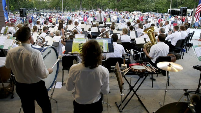 The crowd stands for the National Anthem at the closing of the Appleton City Band's performance Tuesday at Pierce Park in Appleton.