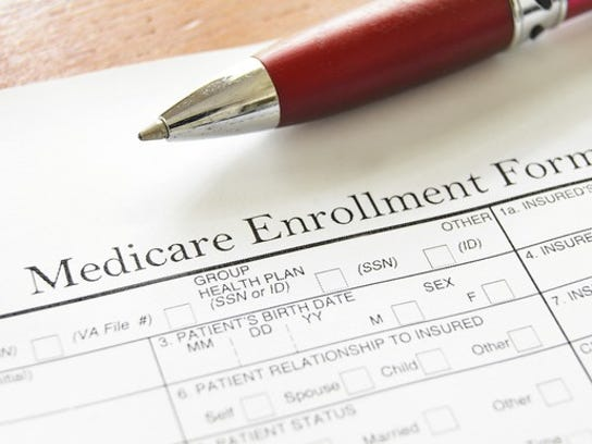 Medicare enrollment form on a wood desk with a red pen on top of the form.