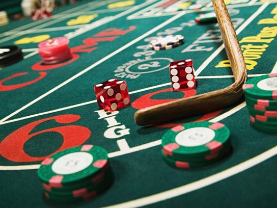 Dice on craps table with chips and the croupier stick collecting the dice.