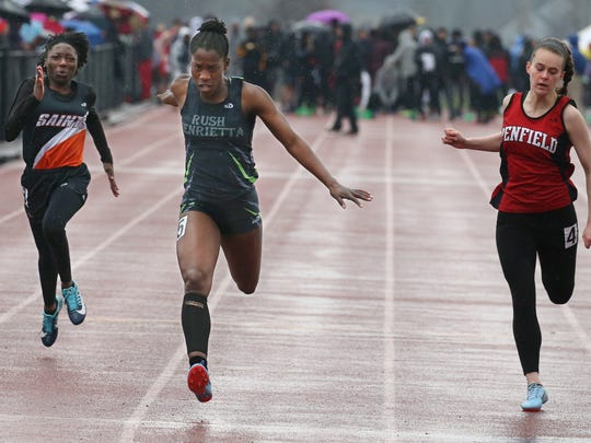 Stephanie Hyde, Rush Henrietta, center, leans for the finish as she wins the girls 100 meter dash ahead of Leilani Whyte, Churchville, left, and Stefani Teglash, Penfield, right.