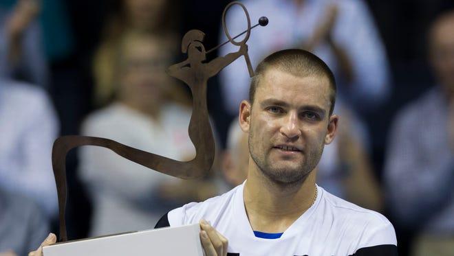 Mikhail Youzhny hoists the trophy after defeating David Ferrer.