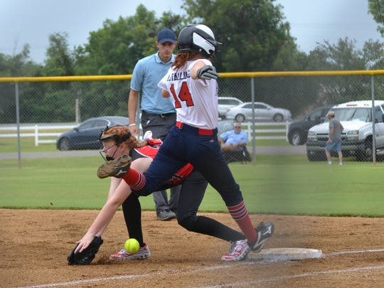 Alexandria Ponytails local host runner Avery Stallings (14) is safe as the ball gets away from the Alabama first baseman Saturday at the Johnny Downs Recreation Complex as part of the Dixie Softball World Series.