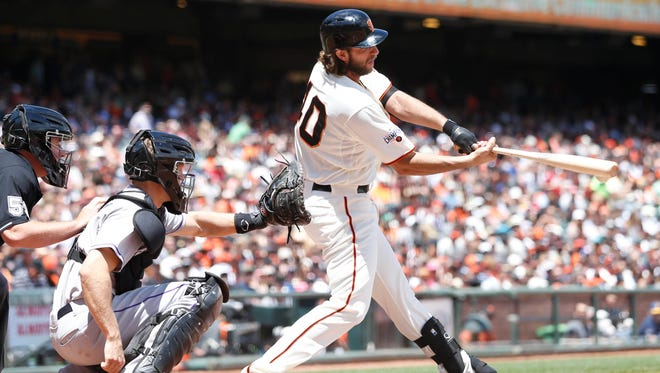 San Francisco Giants starting pitcher Madison Bumgarner (40) hits a single during the third inning against the Colorado Rockies at AT&T Park.